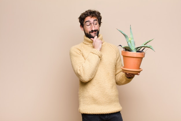 Jeune homme cool tenant une plante de cactus contre un mur plat