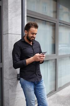 Un jeune homme cool utilise un smartphone. hipster avec une barbe écrit un message dans son téléphone portable. copiez l'espace.