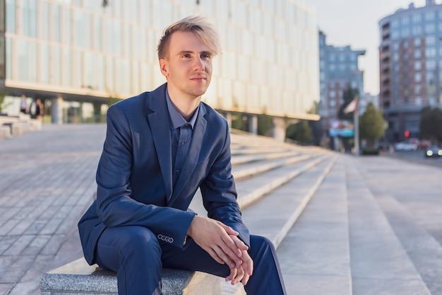 Jeune homme en costume d'affaires se repose devant un immeuble de bureaux