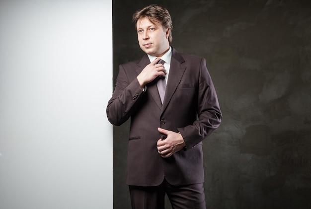 Jeune homme en costume avec bannière pour votre texte sur fond gris grunge