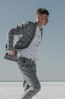 Jeune homme en costume à carreaux gris ajustant sa veste pendant la marche.