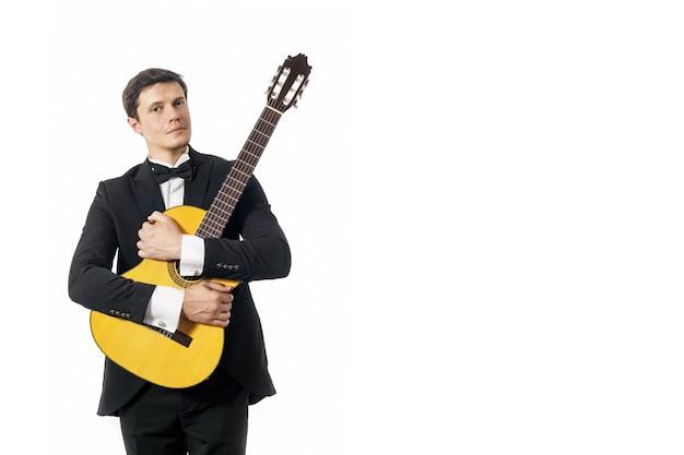 Jeune homme en costume classique noir avec noeud papillon posant avec guitare classique en studio sur blanc