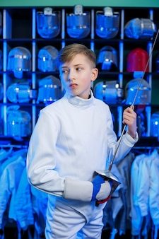 Jeune homme en costume d'escrime avec une épée à la main, sur fond bleu, néon. l'athlète s'entraîne. sports, jeunesse, mode de vie sain.