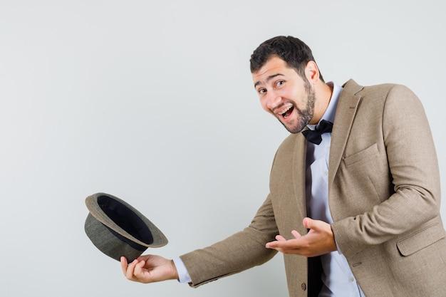 Jeune homme en costume félicitant en enlevant son chapeau et en regardant heureux, vue de face.