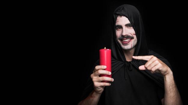 Jeune homme en costume d'halloween avec des rayures sur le visage en tenant la bougie