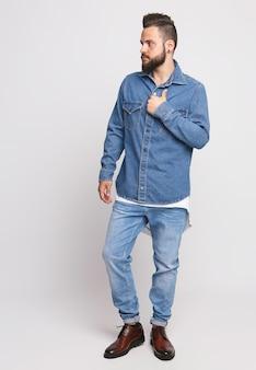 Jeune homme en costume en jean. bel homme en veste en jean et jeans sur fond blanc. photo pour la publicité des jeans et des vestes pour hommes. concept pour la publicité.