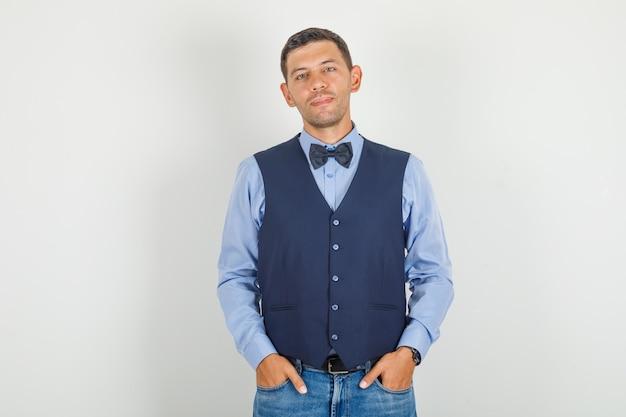 Jeune homme en costume, jeans debout avec les mains dans les poches et à la gaieté