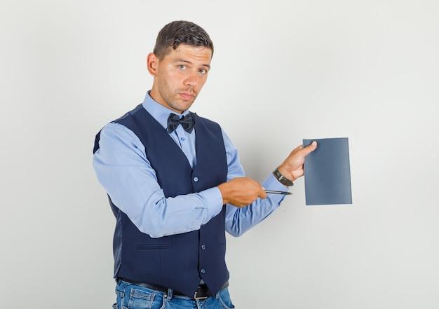 Jeune homme en costume, jeans pointant un stylo au cahier et à la recherche de sérieux