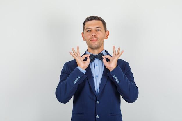 Jeune homme en costume montrant le geste ok et à la satisfaction