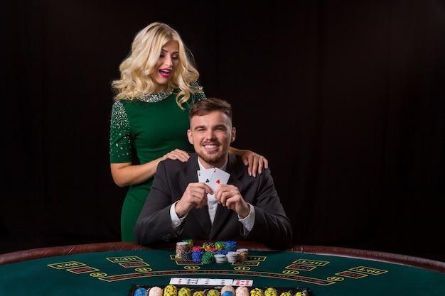 Un jeune homme en costume montre une paire d'as. jouer au poker à table. la jeune femme aime gagner au poker. il regarde la caméra et sourit