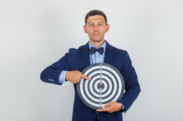 Jeune homme en costume pointant le doigt sur le jeu de fléchettes et à la recherche de sérieux