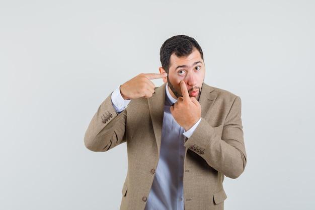 Jeune homme en costume pointant sur la paupière inférieure tirée par le doigt, vue de face.