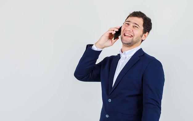 Jeune homme en costume de rire tout en parlant sur smartphone, vue de face.