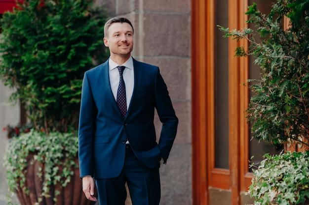 Jeune homme en costume, se tient près d'un bâtiment, garde la main dans sa poche