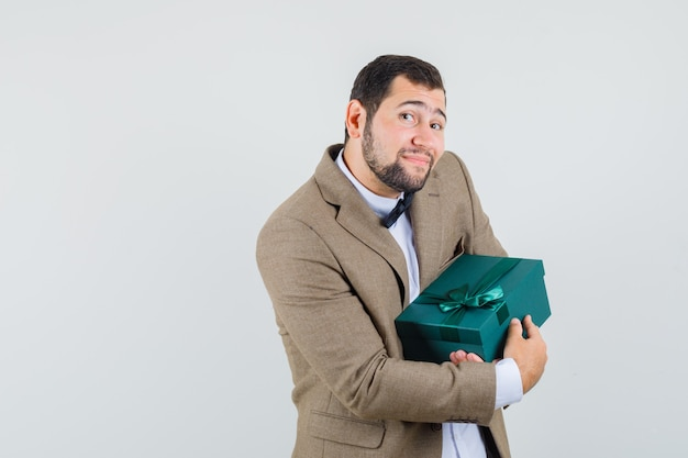 Jeune homme en costume tenant présent fort et à la joyeuse vue de face.