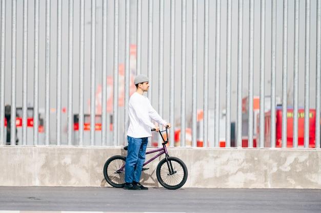 Jeune homme à côté de son vélo posant
