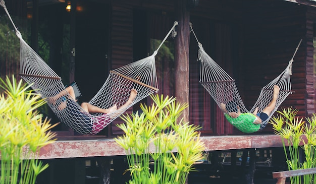 Jeune homme couché dans un hamac blanc dans la station balnéaire et écouter de la musique sur smartphone.