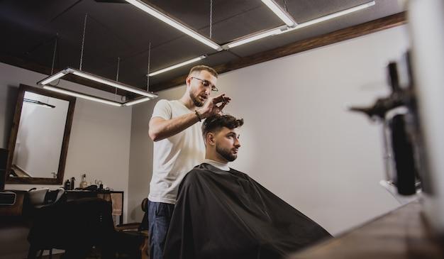 Jeune homme avec coupe de cheveux tendance au salon de coiffure. barber fait la coiffure et la coupe de la barbe.