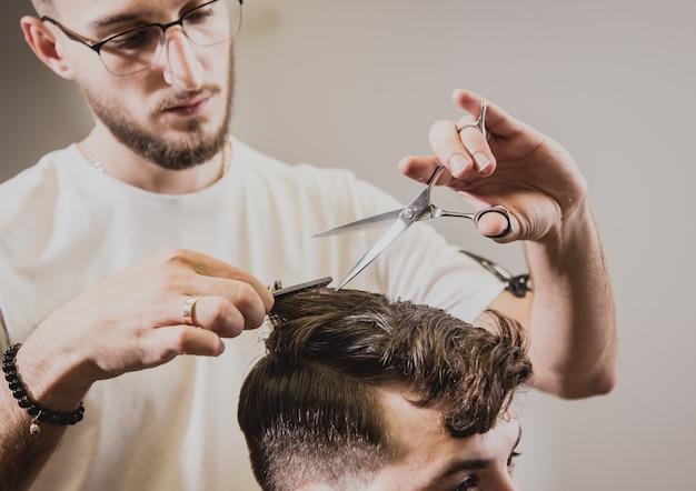 Jeune homme avec coupe de cheveux tendance au salon de coiffure.
