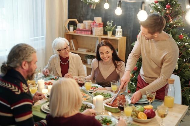 Jeune homme coupe la dinde rôtie en se tenant debout par table servie devant la famille pendant le dîner de noël à la maison
