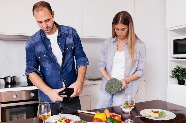 Jeune homme coupe les légumes dans la cuisine