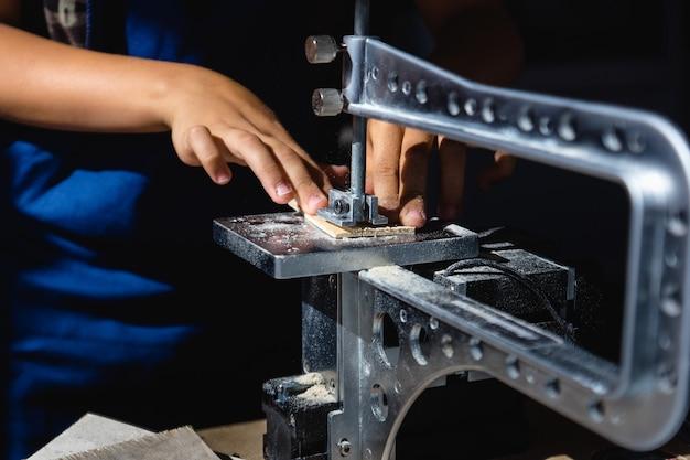 Un jeune homme coupe un motif sur contreplaqué avec une scie électrique