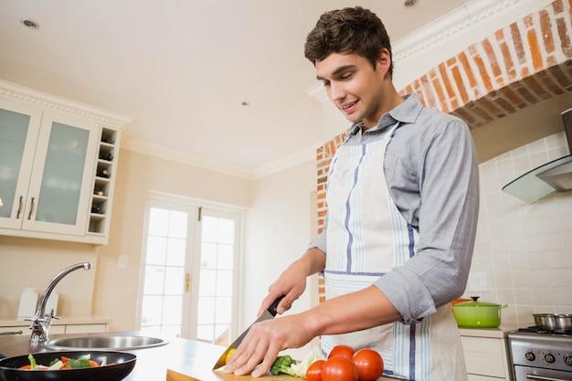 Jeune homme, couper légumes, à, planche planche, dans, cuisine