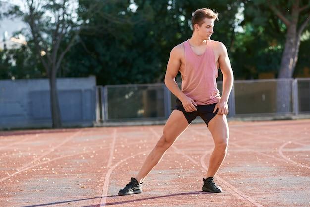 Jeune homme coureur qui s'étend de sa jambe sur la piste de course dans le stade