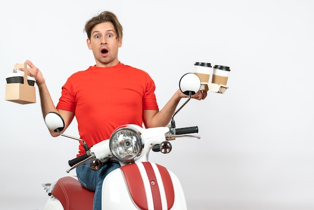 Jeune homme de courrier choqué en uniforme rouge assis sur un scooter tenant des commandes sur le mur jaune