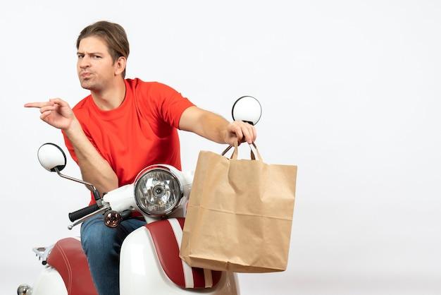 Jeune homme de courrier émotionnel surpris en uniforme rouge assis sur un scooter donnant un sac en papier pointant quelque chose sur le côté droit sur un mur blanc