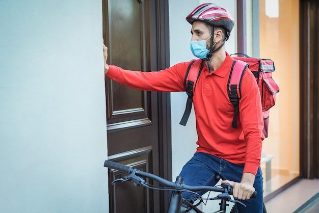 Jeune homme de courrier avec sac à dos thermique et vélo sonnant à la porte - focus sur le visage