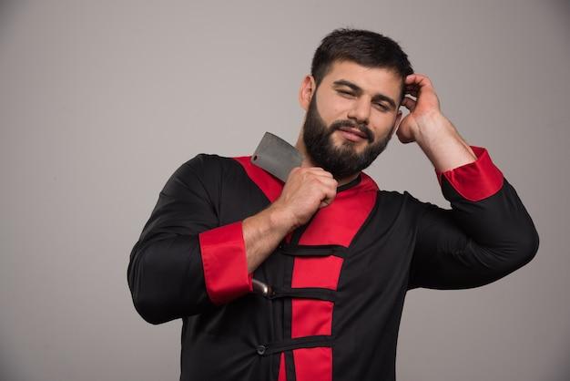Jeune homme avec un couteau bien aiguisé sur mur gris