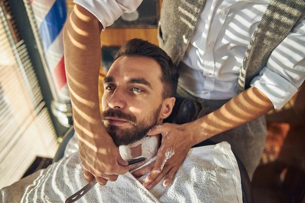 Un jeune homme couvert de crème se rasant avec un rasoir droit par un barbier professionnel