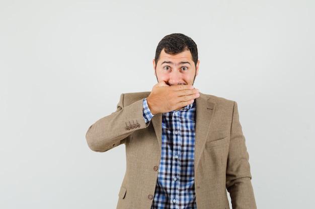 Jeune homme couvrant la bouche avec la main en chemise, veste et à l'optimiste. vue de face.