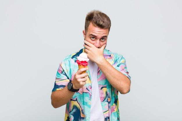 Jeune homme couvrant la bouche avec les mains avec une expression choquée et surprise, gardant un secret ou disant oups