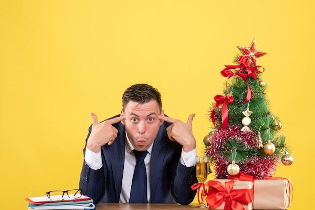 Jeune homme couvrant les doigts son oreille assis à la table près de l'arbre de noël et des cadeaux sur jaune