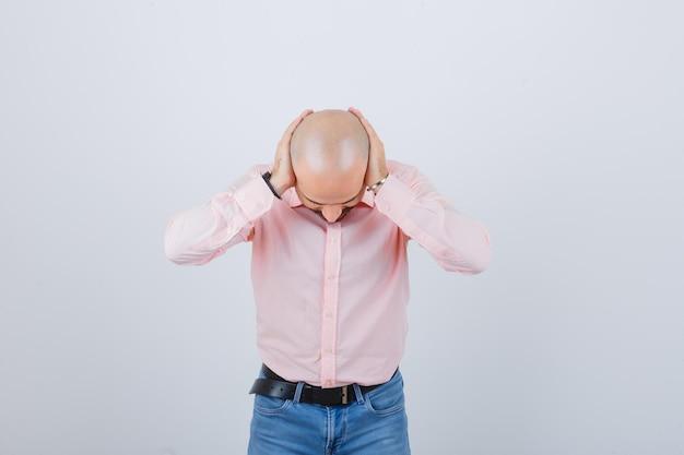 Jeune homme couvrant les oreilles avec les mains
