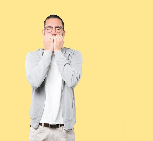 Jeune homme couvrant sa bouche avec ses mains
