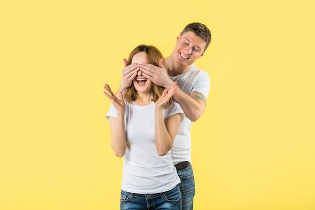 Jeune homme couvrant ses yeux de copine avec deux mains, haussant les épaules sur fond jaune