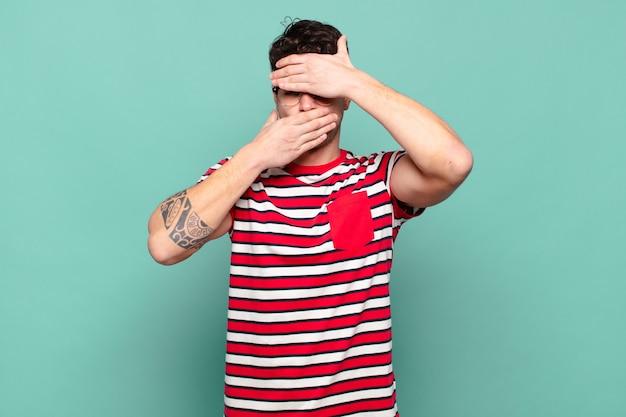 Jeune homme couvrant le visage avec les deux mains disant non à la caméra ! refuser des photos ou interdire des photos