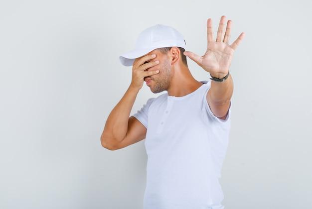 Jeune homme couvrant les yeux et faisant le geste d'arrêt en t-shirt blanc, casquette, vue de face.
