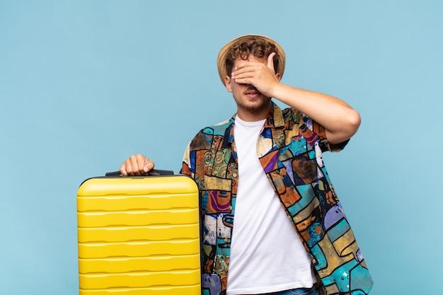 Jeune homme couvrant les yeux d'une main se sentant effrayé ou anxieux, se demandant ou attendant aveuglément une surprise. concept de vacances