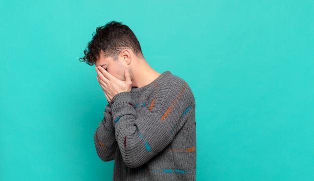 Jeune homme couvrant les yeux avec les mains avec un regard triste et frustré de désespoir, pleurant, vue latérale