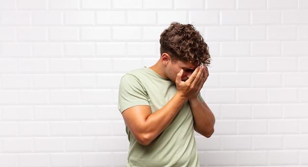 Jeune homme couvrant les yeux avec les mains avec un regard triste et frustré de désespoir