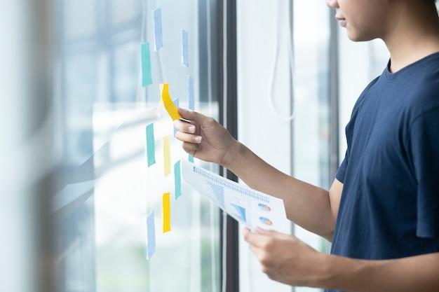 Jeune homme créatif lisant des notes autocollantes sur le mur de verre.
