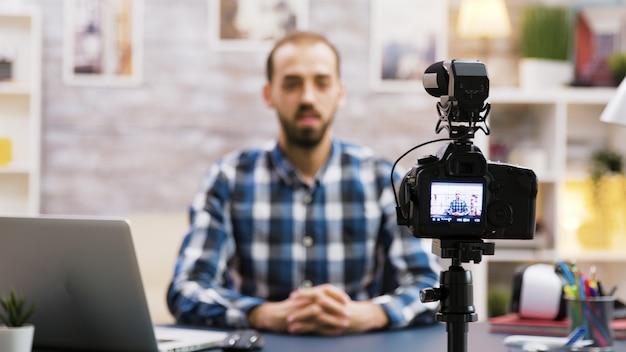 Jeune homme créatif parlant devant la caméra. zoom en effet de prise de vue.