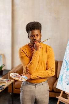 Jeune homme créatif tenant un pinceau en pensant à sa peinture