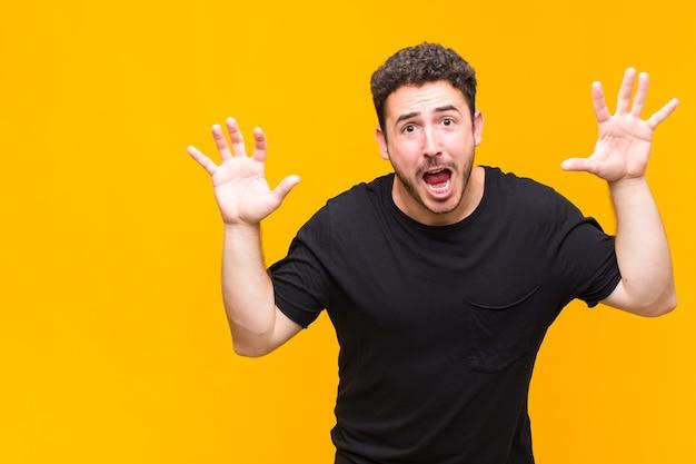 Jeune homme criant de panique ou de colère, choqué, terrifié ou furieux, avec les mains à côté de la tête