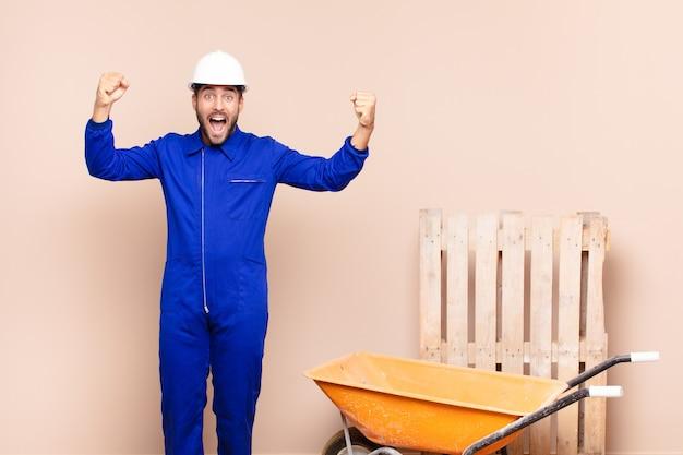 Jeune homme criant triomphalement, ressemblant à un gagnant excité, heureux et surpris, célébrant le concept de construction