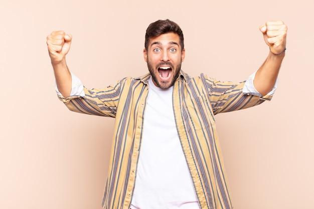 Jeune homme criant triomphalement, ressemblant à un gagnant excité, heureux et surpris, célébrant